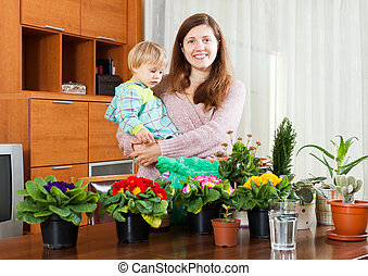 Mother and baby with flowering plants - Female gardener with...