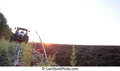 gray tractor rides on the field - gray tractor rides on the...