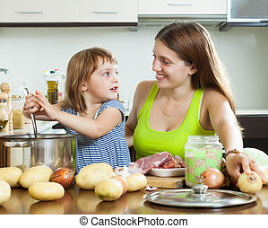 Happy mother with child cooking soup from meat and...