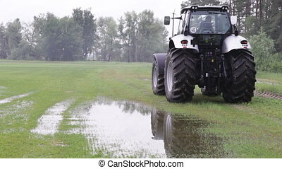 gray tractor rides on the green field puddles on a...