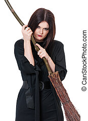 Young witch - Furious young witch with broom isolated on...