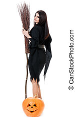 Young witch - Young sexy witch with broom and pumpkin over...