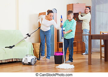 Happy family vacuuming at home - Happy family of three...