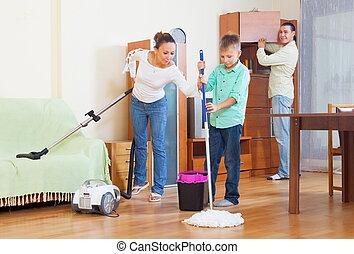 Happy family vacuuming at home - Happy family of three...