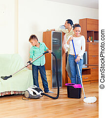 Ordinary family doing cleaning with cleaning equipment in...