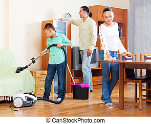 parents with teenage son doing house cleaning in living room...