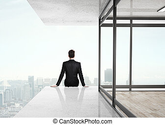 businessman sitting on skyscrapper and looking to city
