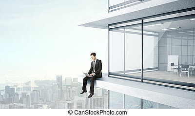 man with laptop - young man sitting on skyscrapper with...