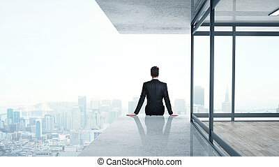 man sitting on skyscrapper - young man sitting on...