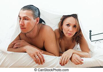 Unhappy couple under sheet