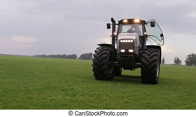 gray tractor rides on the green field on a background of...