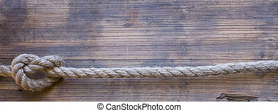 wooden board with a rough texture and a rope with a knot...
