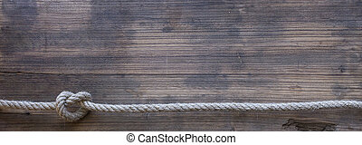 wooden board with a rough texture and a rope with a knot....