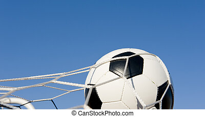 Soccer or Football in Goal - A traditional soccer ball or...