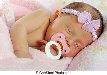 Binky Baby - Close up of an adorable newborn wrapped in a...