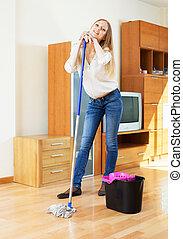 Blonde woman washing parquet