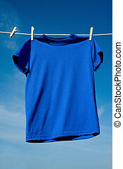A Blue T-Shirt - a blue T-shirt hanging on a clothesline on...