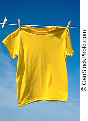 a Yellow T-Shirt - A yellow colored T-shirts hanging on a...