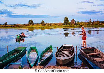 Belarusian Boy Fishing From Old Boats At Sunset Of A Summer...