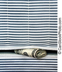 Money in the Mattress - A roll of money tucked in a mattress...