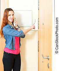 Smiling red-haired girl using house videophone indoor -...