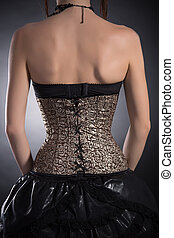 Rear view of woman wearing golden corset