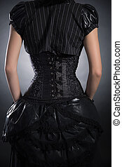 Back view of woman wearing black rose corset and Victorian...