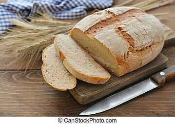 Sliced  bread on cutting board closeup on wooden background