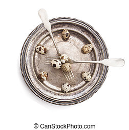 Clock made of quail eggs on silver plate with forks, isolated on white background
