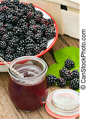 Freshly harvested forest blackberries in a bowl with a glass...