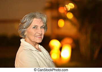 Woman on night street - Portrait of old woman on night...
