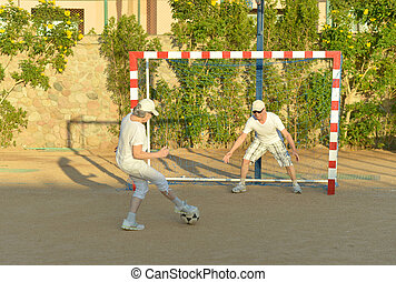 Active couple playng football - Active senior couple playng...