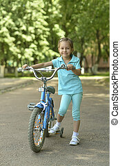 Little girl with bicycle in summer