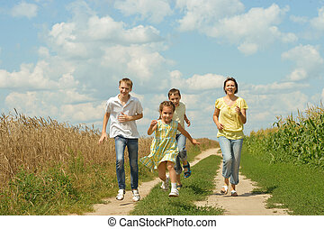 Family running on a dirt road - Happy family running on a...