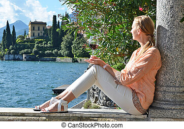 Girl with a glass of wine at the villa Monastero. Lake Como,...