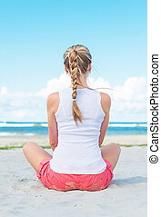 Pigtailed girl sitting on the beach and meditating.