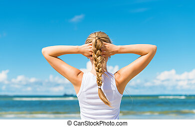 Pigtailed girl on the beach. View from the back.