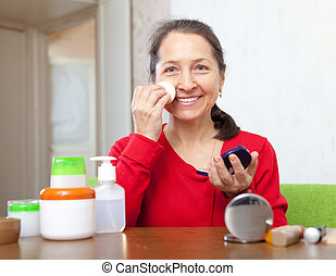 mature woman puts facepowder on face - mature woman in red...