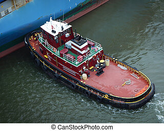 Tugboat pushing a vessel to come alongside