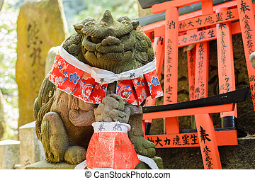 Stone lion statue. - Stone lion statue in front of Torii.