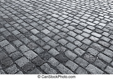 Old wet stone paved avenue street road, low angle after rain