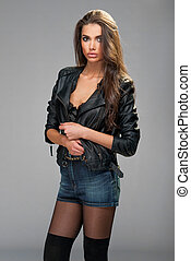 Portrait of beautiful brunette woman fashion model  wearing black leather coat posing at studio about the wall