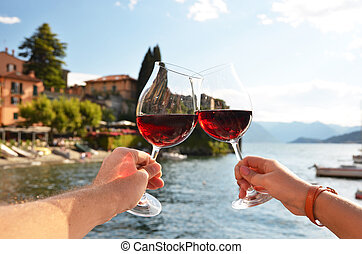 Two wineglasses in the hands Varenna town at the lake Como,...