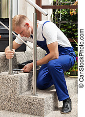 Repairman at work - Young strong repairman in protective...