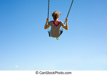 Young Girl on Swing - A young girl playing on a swingset in...