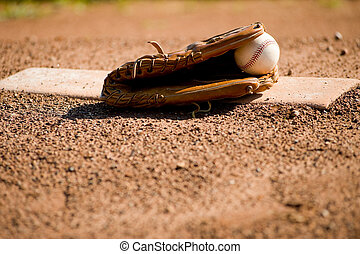 Baseball Glove and Ball on Pitcher\'s Mound - A brown...