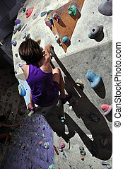 Child exercising at bouldering gym - Litle girl exercising...