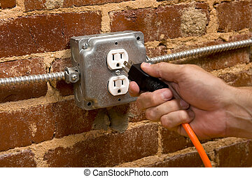 Plugging in an Extension cord - a man\'s hand plugging in an...