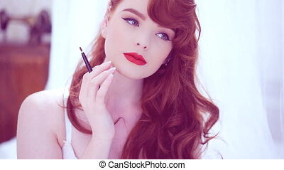 Beautiful redhead applying red lip gloss - Beautiful young...