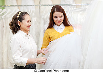 Two women chooses bridal veil at wedding boutique Focus on...